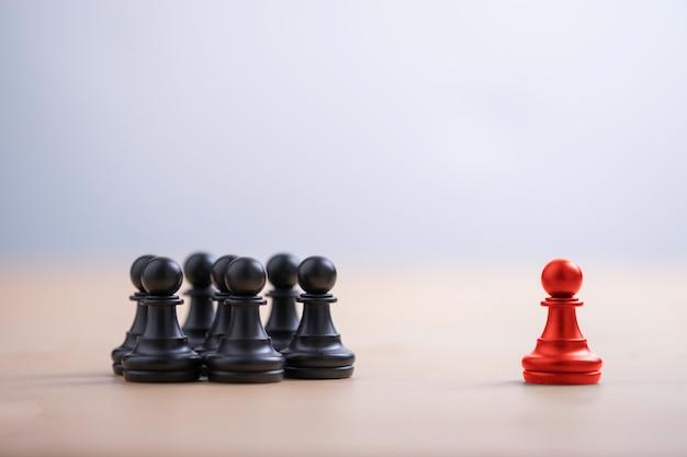 El ajedrez peón rojo salió del grupo para mostrar diferentes ideas de pensamiento y liderazgo. cambio tecnológico e interrupción del negocio para un nuevo concepto normal.