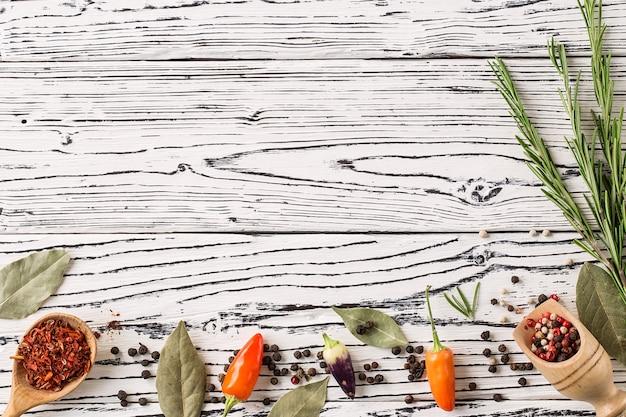 Ají y ramitas de romero con hojas de laurel en madera t