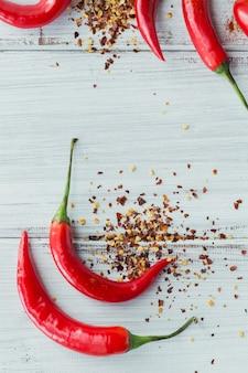 Ají rojo orgánico fresco crudo y una variedad de especias en la superficie de madera blanca