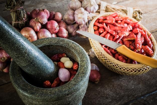 Ají seco y cebolla roja y ajo y mortero de piedra sobre un fondo de madera viejo