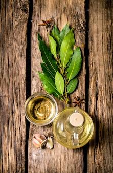 El ajo y la ramita de laurel con aceite de oliva. sobre fondo de madera. vista superior