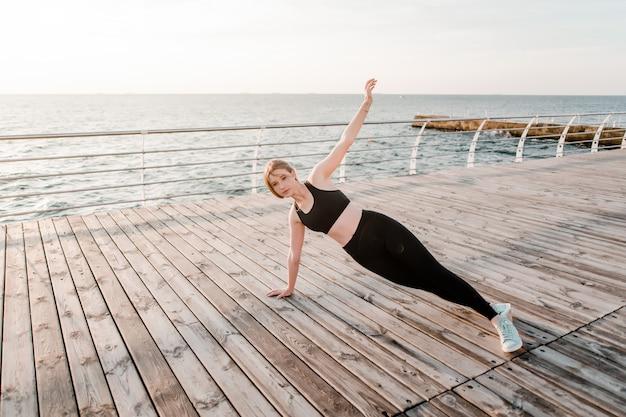 Ajuste adolescente haciendo ejercicios deportivos en la mañana en la playa