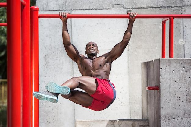 Ajuste atleta haciendo ejercicios en el estadio. hombre afro al aire libre en la ciudad. tire hacia arriba de los ejercicios deportivos. fitness, salud, concepto de estilo de vida