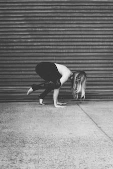 Ajuste atractivo modelo femenino practicando yoga cerca de un garaje en la acera rodada en escala de grises