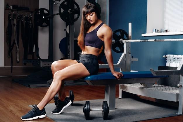 Ajuste chica en el gimnasio sentado en un aparato de entrenamiento