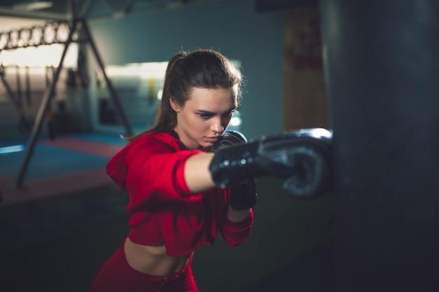 Ajuste delgado joven hermosa mujer morena boxeo en ropa deportiva