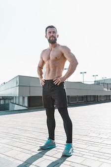 Ajuste fitness hombre posando en la ciudad