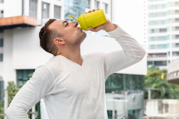Ajuste hombre caucásico en ropa deportiva agua potable después de entrenar fuera.
