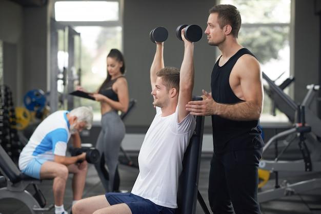 Ajuste hombre trabajando en el gimnasio con entrenador personal.
