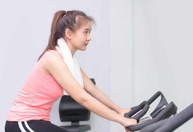 Ajuste joven asiática con bicicleta estática en el gimnasio.