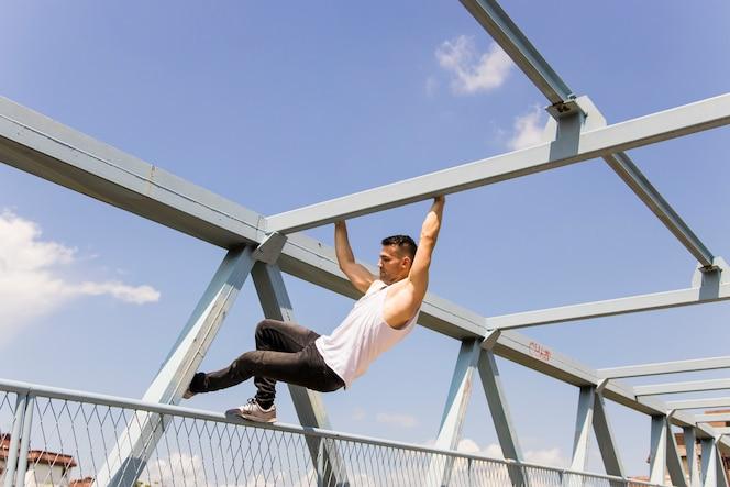 Ajuste joven escalada en el techo de un puente