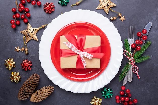 Ajuste de lugar de mesa de navidad con placa roja, caja de regalo, cubiertos con decoraciones festivas estrella arco sobre fondo de piedra