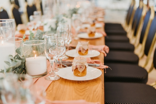 Ajuste de la mesa de boda en un restaurante decorado con flores y velas