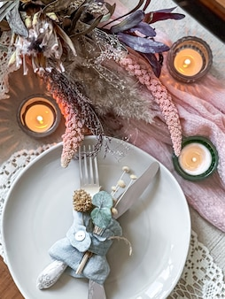 Ajuste de la mesa para una cena romántica, boda o cualquier ocasión con velas y flores secas como decoración.