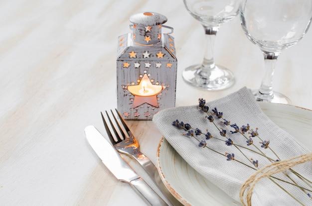 Ajuste de la mesa festiva con velas y lavanda.