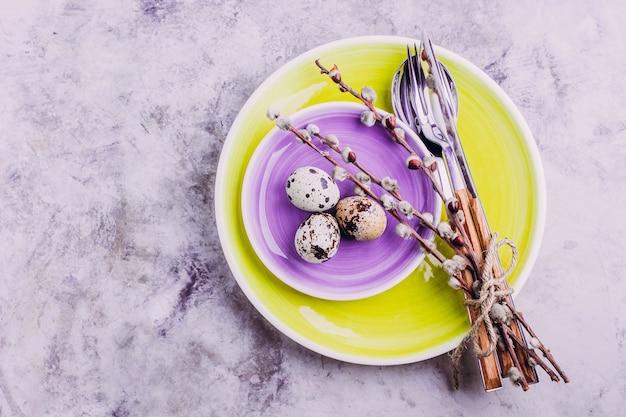 Ajuste de la mesa de pascua. plato amarillo y morado, cubiertos, huevos de codorniz y sauce.