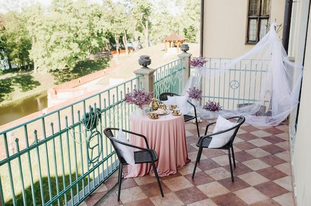 Ajuste de la mesa del té de la mañana delicada con flores lilas en el castillo de nesvizh, cucharas antiguas y platos sobre la mesa con un mantel rosa.