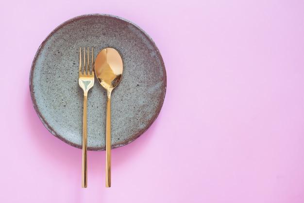 Ajuste de la mesa, vajilla de cerámica, cuchara y tenedor sobre fondo de color rosa pastel