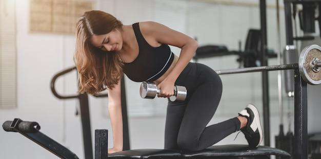 Ajuste mujer atlética asiática levantando pesas dentro del gimnasio en casa