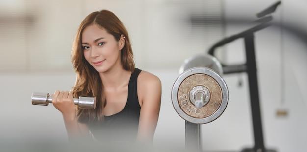 Ajuste mujer atlética asiática levantando pesas dentro del gimnasio y sonriendo a la cámara