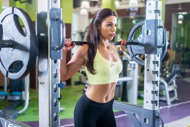Ajuste mujer haciendo ejercicio de press de hombros con una barra de pesas máquina smith en el gimnasio.