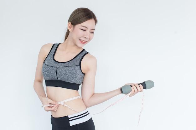 Ajuste saludable y mujer asiática firme midiendo su cintura mirando cinta métrica