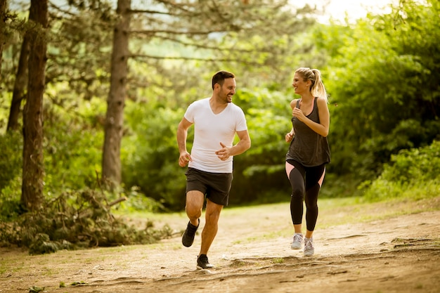 Ajuste saludable y pareja deportiva corriendo en la naturaleza.