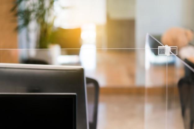 Ajuste del separador de plexiglás acrílico en el escritorio de la oficina.