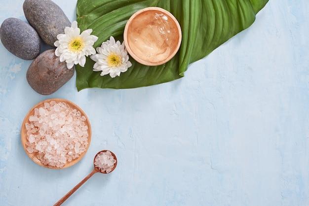 Ajuste de spa con crema cosmética, gel, sal de baño y hojas de helecho sobre fondo azul.