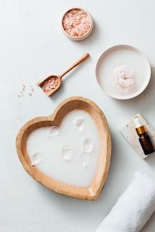 Ajuste de spa con cuenco de leche de arroz, flores, sal, jabón, aceite y toalla sobre fondo blanco.
