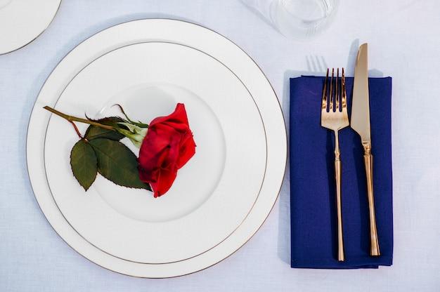Ajuste de la tabla, cubiertos y rosa roja en el primer plano de la placa, vista superior, nadie. decoración de banquete de lujo, mantel blanco, vajilla al aire libre