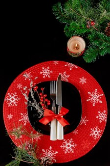 Ajuste de la tabla festiva para la cena de navidad sobre fondo negro. decoraciones navideñas navideñas. vista superior.