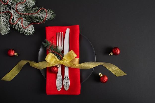 Ajuste de la tabla de navidad con una servilleta roja sobre fondo negro. vista superior. copie el espacio.