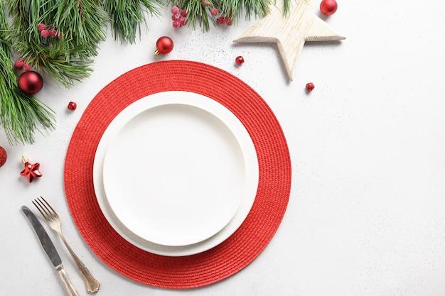 Ajuste de la tabla navideña con adornos navideños blancos y rojos