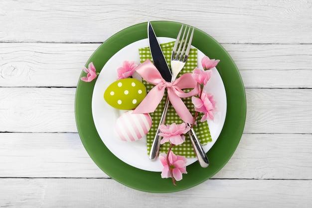 Ajuste de la tabla de pascua con flores de primavera y cubiertos. fondo de vacaciones