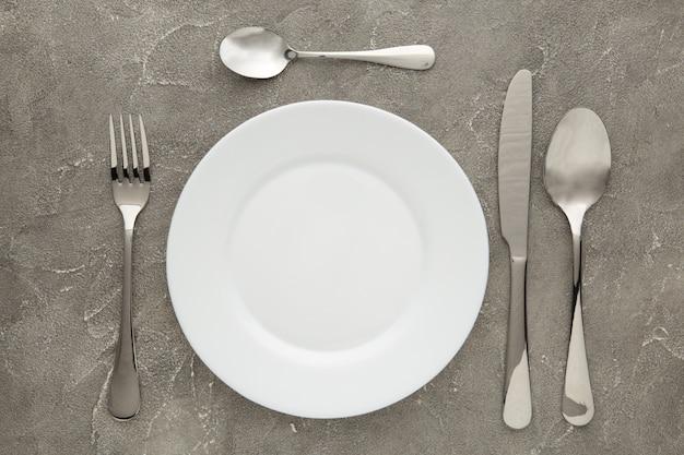 Ajuste de la tabla con plato blanco y cubiertos