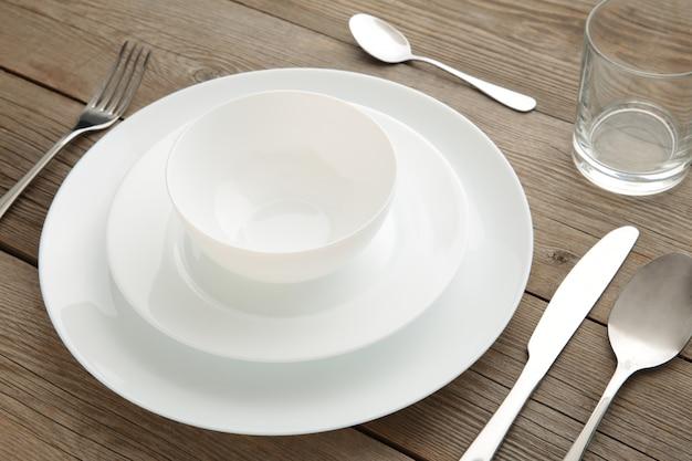 Ajuste de la tabla con platos y cubiertos blancos