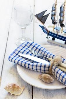 Ajuste de la tabla del verano con la decoración del mar en un fondo de los tableros blancos