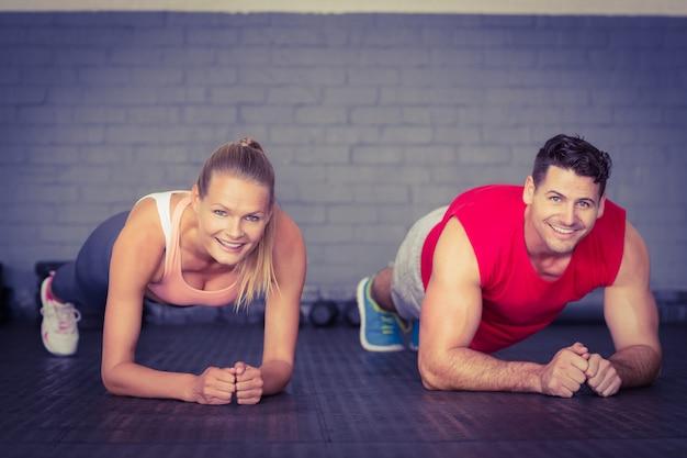 Ajuste tablones sonrientes de los pares junto en gimnasio en gimnasio del crossfit