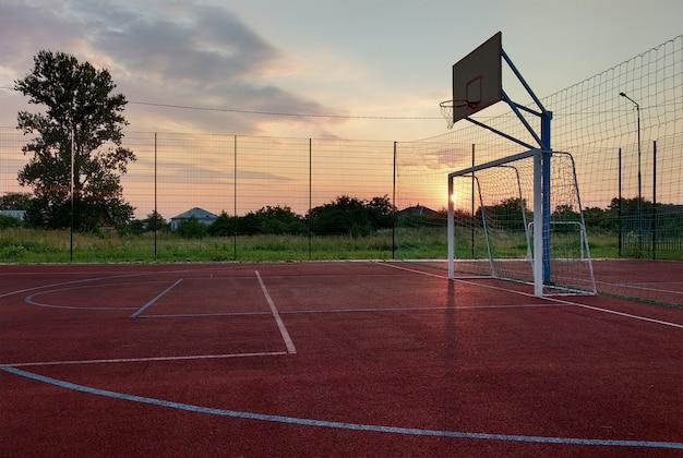 Al aire libre mini cancha de fútbol y baloncesto con portón de pelota y canasta rodeada con valla protectora alta.