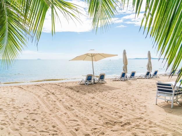 Al aire libre con paraguas y silla en la hermosa playa tropical y el mar