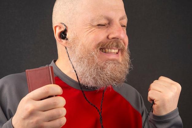 Al hombre barbudo le gusta escuchar su música favorita en casa con un reproductor de audio