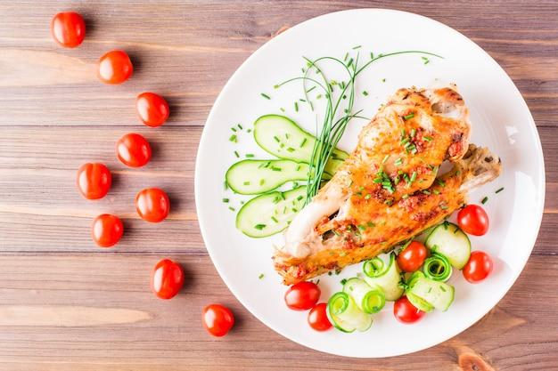 Al horno en un ala de pavo de especias, rodajas de pepino y tomates cherry en un plato sobre una mesa de madera. vista superior