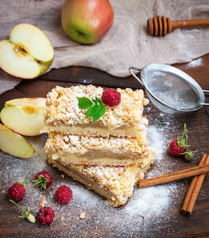 Al horno rebanadas de pastel con manzanas en una tabla de madera marrón
