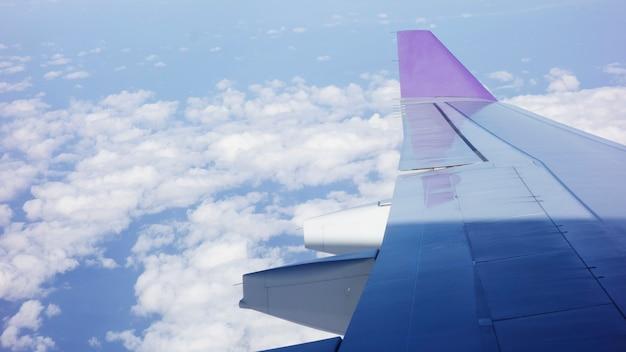 Ala de un avión volando por encima de las nubes de la mañana