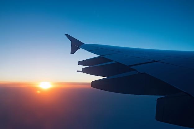 Ala de avión en vuelo en la luz del atardecer con nubes