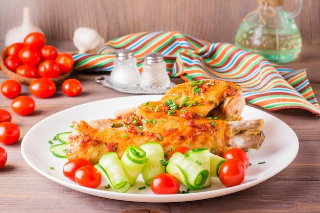 Ala de pavo al horno, rodajas de pepino y tomates cherry en un plato sobre una mesa de madera