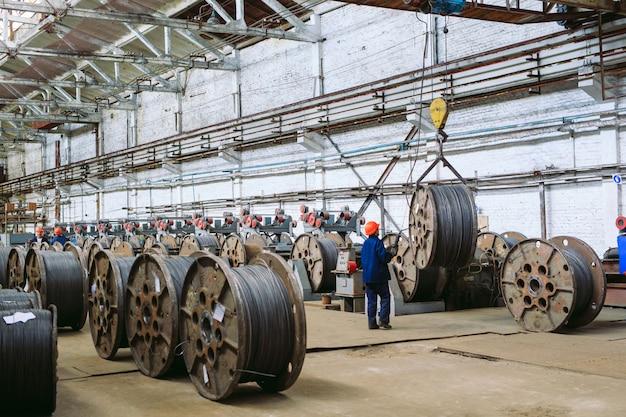 Alambrón, guarniciones en almacenes. trabajador junto a un paquete con catalkoy. almacén industrial en la planta metalúrgica.