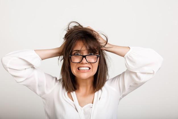 Alarmada, angustiada mujer en problemas para despeinar el cabello
