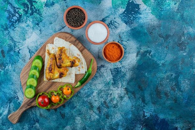 Alas al horno, lavash y verduras sobre una tabla de cortar, sobre fondo azul.